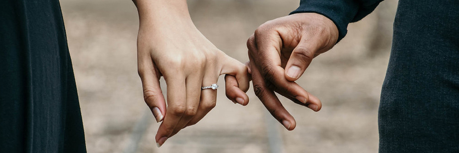 Christian couple holding hands with wedding ring